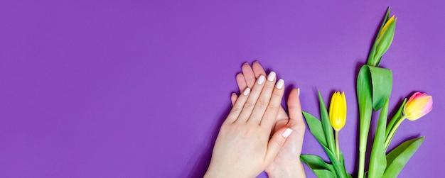 Manicure feminina em um fundo brilhante. fundo roxo com flores. bandeira.