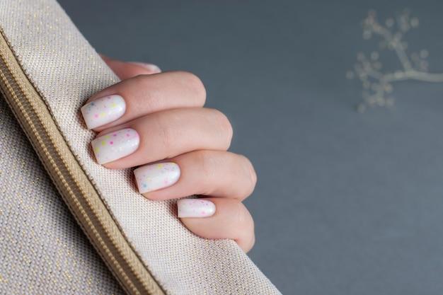 Manicure feminina leve com efeito de confete, close-up da mão.