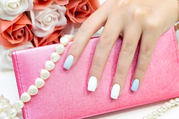 Manicure feminina na moda elegante. belas mãos de uma jovem em um fundo de flores e miçangas de pérolas