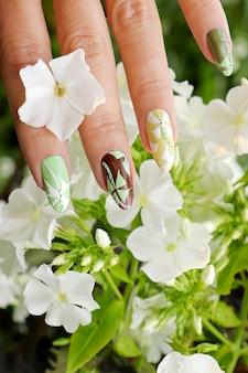 Manicure floral pastel com um desenho nas unhas