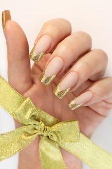 Manicure francesa clássica dourada com um laço na mão