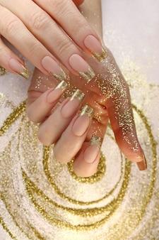 Manicure francesa de moda dourada em unhas compridas com glitter dourado.