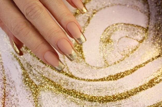 Manicure francesa na moda dourada em unhas compridas com lantejoulas.