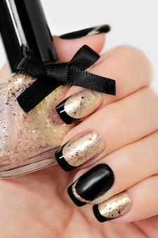 Manicure francesa preta e dourada com esmalte na mão closeup.