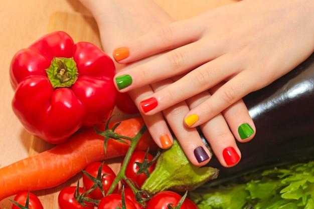 Manicure infantil com design de verniz colorido para as unhas na menina com pepino, tomate, cenoura, berinjela de alimentos diferentes. Foto Premium