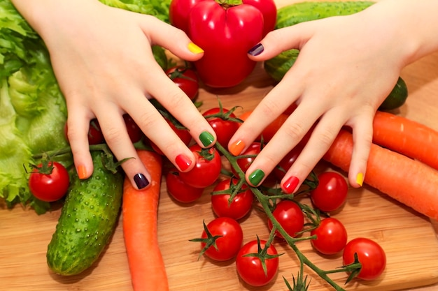 Manicure infantil com design de verniz colorido para as unhas na menina com pepino, tomate, cenoura, berinjela de alimentos diferentes.