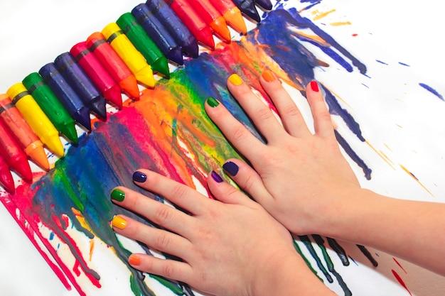 Manicure infantil de arco-íris misto e desenho de closeup de lápis de cera sobre um fundo claro.