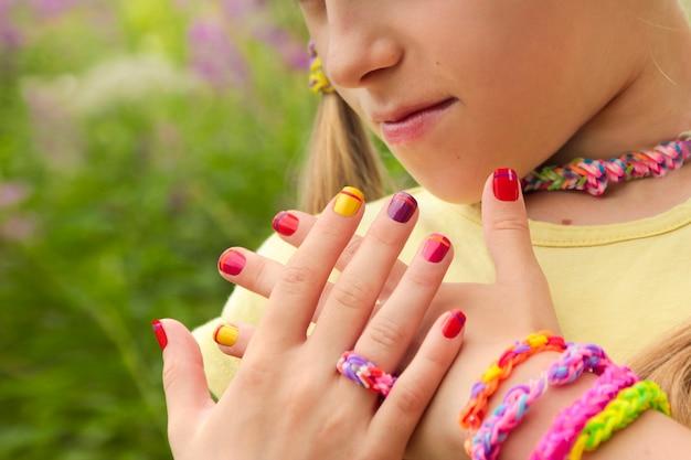 Manicure infantil multicolorida com listras em uma garota clara com elásticos em um dia de verão