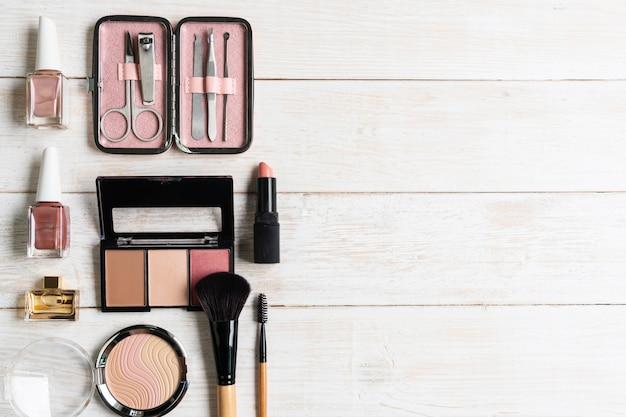 Manicure instrumentos e ferramentas na caixa cor-de-rosa com verniz para as unhas, cosmético no fundo de madeira branco, vista superior, spce da cópia, conceito da beleza.