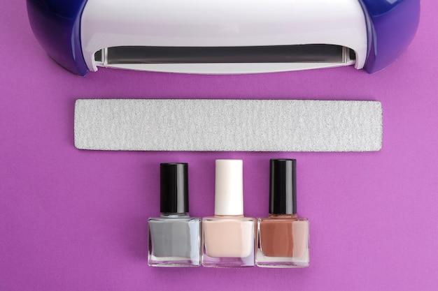 Manicure. lâmpada ultravioleta, lixas de unhas e esmaltes em um fundo roxo da moda. acessórios e ferramentas de manicure para unhas. vista do topo