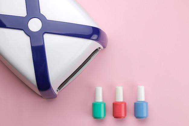 Manicure. lâmpada uv e esmalte em um fundo rosa suave. acessórios e ferramentas de manicure para unhas. vista do topo