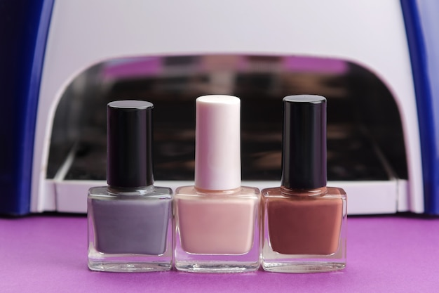 Manicure. lâmpada uv e esmalte em um fundo roxo da moda. acessórios e ferramentas de manicure para unhas.