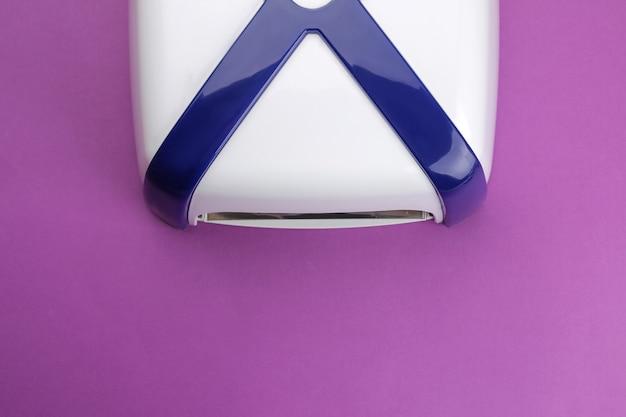 Manicure. lâmpada uv em fundo roxo tendência. acessórios e ferramentas de manicure para unhas. vista do topo