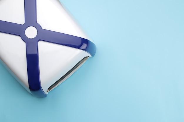 Manicure. lâmpada uv em um fundo azul tendência. acessórios e ferramentas de manicure para unhas. vista do topo