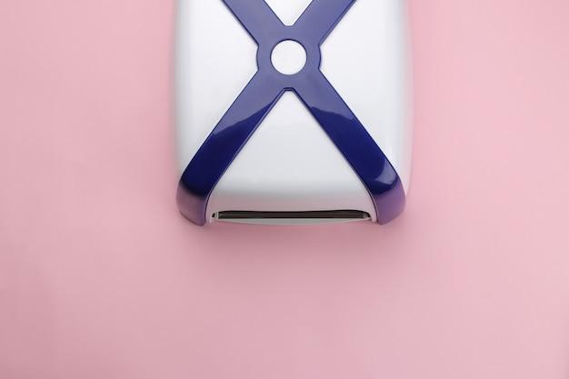 Manicure. lâmpada uv em um fundo rosa suave. acessórios e ferramentas de manicure para unhas. vista do topo