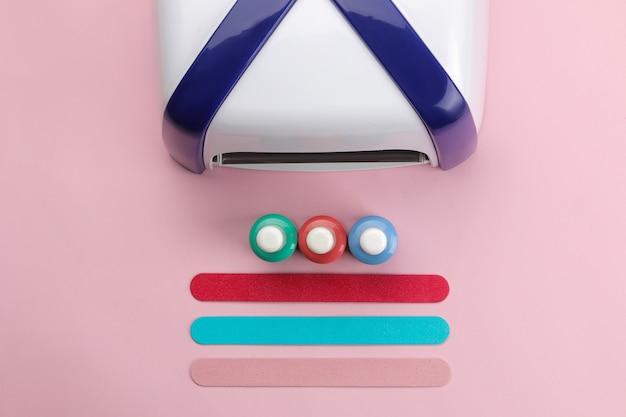 Manicure. lâmpada uv, limas e esmaltes de unha em um fundo rosa suave. acessórios e ferramentas de manicure para unhas. vista do topo