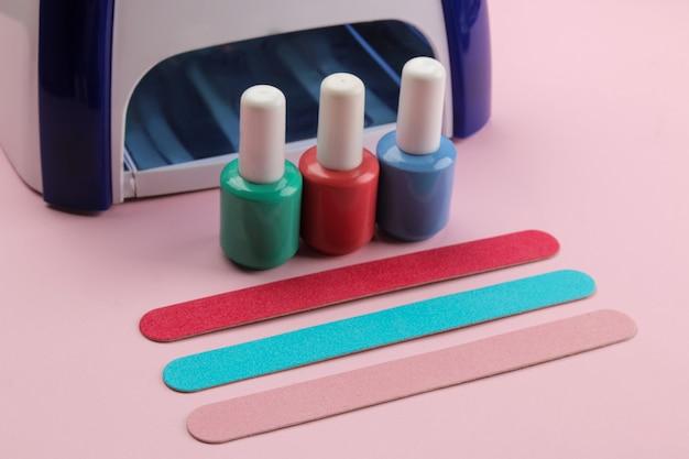 Manicure. lâmpada uv, limas e esmaltes de unha em um fundo rosa suave. acessórios e ferramentas de manicure para unhas.