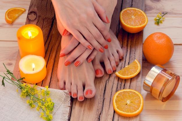 Manicure laranja em torno de laranjas e velas