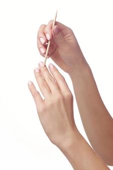 Manicure limpando cutícula nos dedos femininos com bastão cosmético