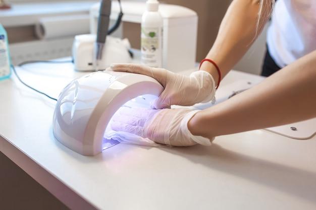 Manicure limpando seu lugar para atender um novo cliente. mesa de salão esterilizante para prevenir infecções.