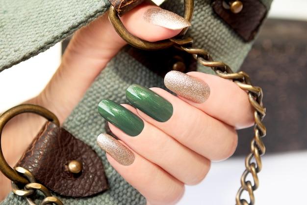 Manicure longa com esmalte verde e dourado