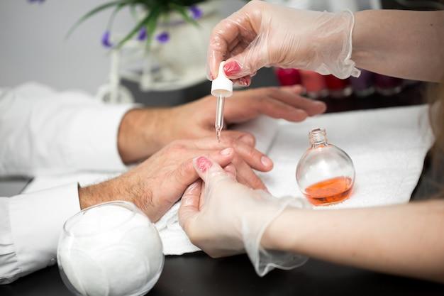 Manicure, mãos spa óleo de cutícula. homem bonito mãos closeup. unhas bem cuidadas. mãos de beleza. tratamento de beleza.