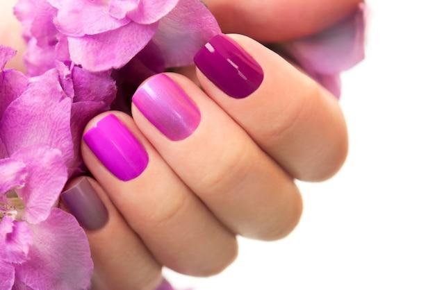 Manicure marrom roxa curta em mão feminina