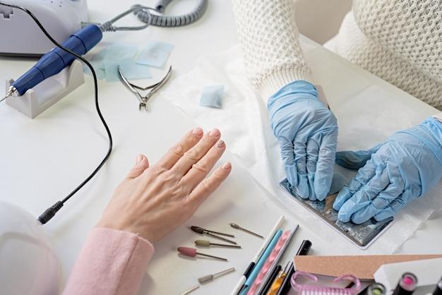 Manicure mestre em máscara e luvas fazendo estamparia na cliente