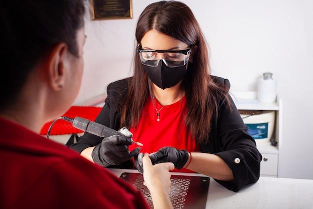 Manicure mestre em óculos de proteção e máscara