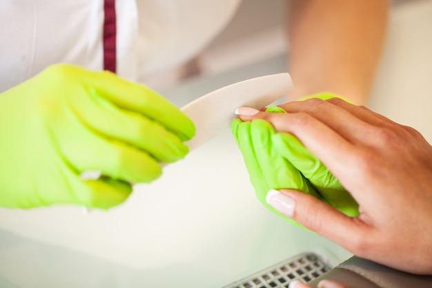 Manicure. mestre hábil de manicure segurando o arquivo em suas mãos enquanto trabalhava em seu salão de beleza