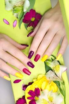 Manicure moderna com cores de esmalte fosco e brilhante com pequenas flores decorativas em um fundo verde claro.