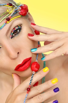 Manicure multicolor e maquiagem criativa em uma garota com joias de miçangas