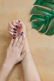 Manicure na moda roxo escuro nas mãos de uma menina. folhas de mãos de mulher em uma mesa de madeira com palmeira. o conceito de cuidados com a pele, cremes naturais para as mãos