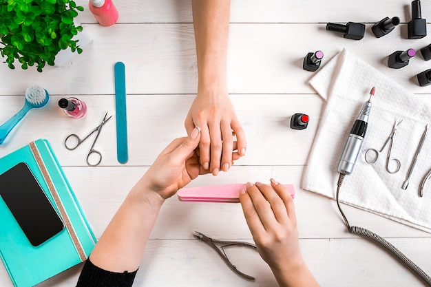 Manicure para a cliente. close das mãos de uma manicure e cliente em um fundo de madeira