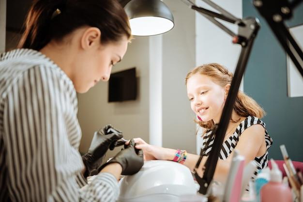 Manicure para a filha. mãe trabalhando como unha artista fazendo manicure para sua linda filha adolescente