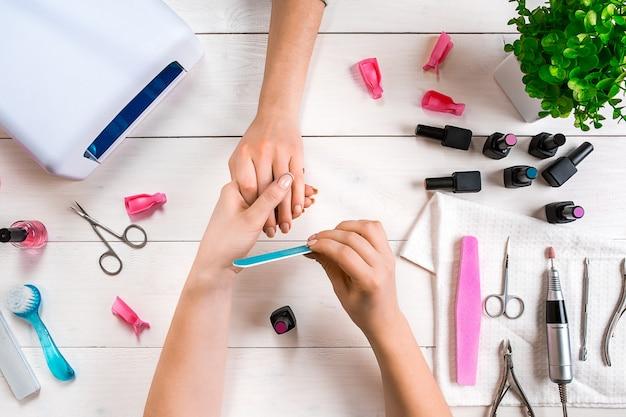 Manicure para o cliente, close up das mãos de uma manicure e cliente em um fundo de madeira