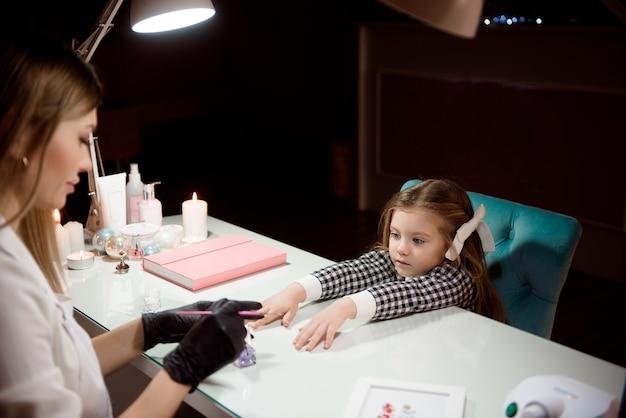 Manicure para uma garota em um salão de beleza.