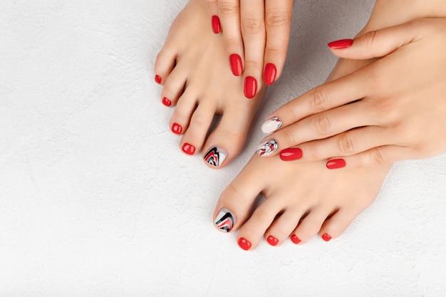 Manicure, pedicure conceito de salão de beleza. mãos e pés da mulher em cinza