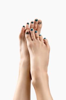 Manicure, pedicure conceito de salão de beleza. os pés da mulher em fundo branco