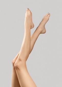 Manicure, pedicure conceito de salão de beleza. os pés da mulher em fundo cinza