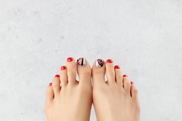 Manicure, pedicure conceito de salão de beleza. pés da mulher em cinza