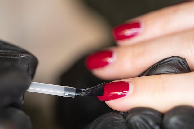Manicure pinta as unhas pintadas. mulher manicure mestre em luvas está polindo as unhas do cliente usando uma lima. trabalhando jovem mulher no salão de cosmetologia, clínica.