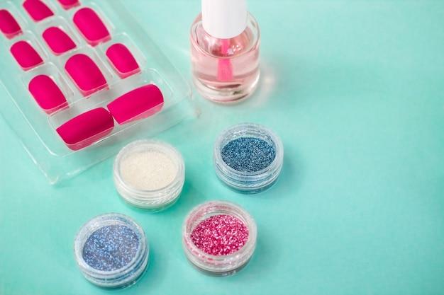 Manicure plana sobre uma mesa verde. esmaltes, brilhos, esmaltes em gel e unhas postiças, pontas de unhas