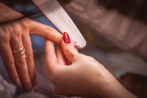 Manicure. prego mestre: serragem processando a borda da unha
