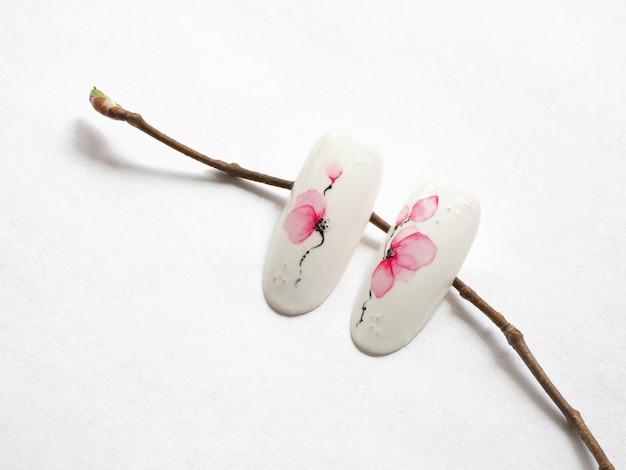 Manicure primavera. dicas com design de flores de primavera em uma parede branca