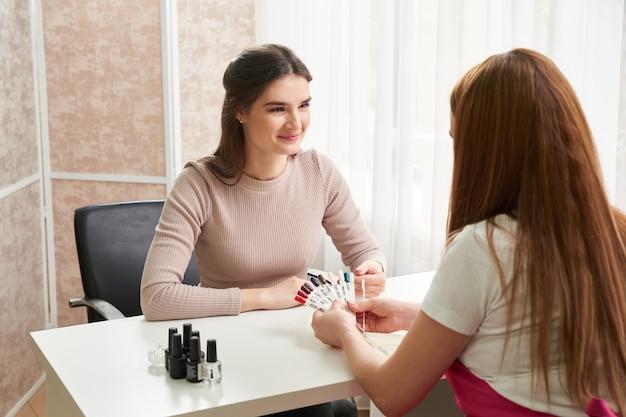 Manicure profissional mostrando esmalte colorido para conferir o resultado final. técnica de unhas apresentando paleta de cores de serviços de unhas em loja de salão de beleza. conceito de beleza e moda.