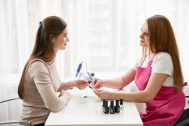 Manicure profissional mostrando esmaltes coloridos para conferir o resultado final. técnica de unhas apresentando paleta de cores de serviços de unhas em loja de salão de beleza. conceito de beleza e moda.