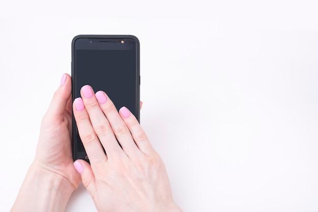 Manicure rosa suave. mãos femininas com um smartphone