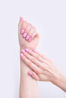 Manicure rosa suave. mãos femininas em branco