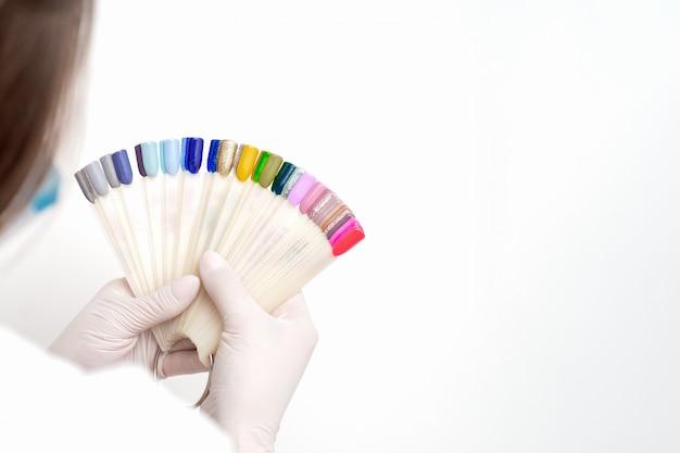 Manicure segurando amostras de cores de unhas.